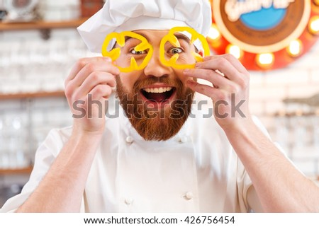Cheerful amusing holding slices of yellow bell pepper in front of his eyes - stock photo