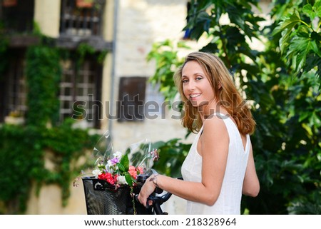 cheerful and attractive young woman riding bicycle during  summertime