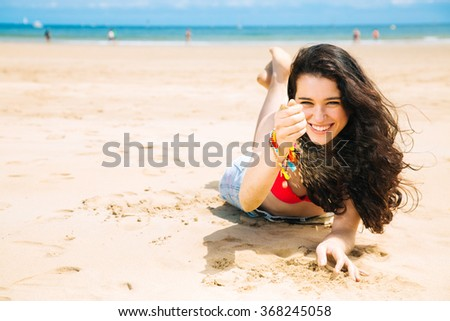 Cheerful and beautiful young woman lying on the beach playing with the sand - stock photo