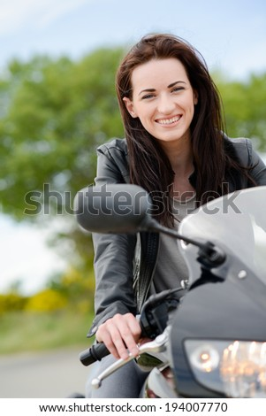 cheerful and beautiful young woman riding motorbike