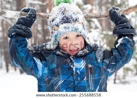 Cheerful and happy boy in the snow in the winter play with big stick - stock photo