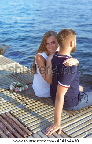 Cheerful and happy evening. Top view of young beautiful couple bonding to each other while sitting at the sea - stock photo