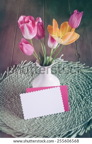 Cheerful and Pretty Orange and Pink Spring Tulips in a White Vase on a Table with Notecard blank for your words, text, copy.  Vertical looking down from above view, vintage instagram faded filter  - stock photo