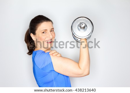 Cheerful and proud adult woman in bright blue sports outfit lifting weights, white background, copy space