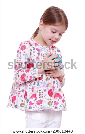 Cheerful and smiling little girl holding and offering globe - stock photo