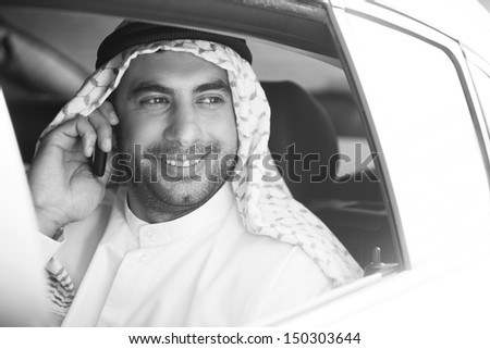 Cheerful Arab businessman. Black and white image of smiling Arab businessman sitting on the back seat of car and talking on the mobile phone - stock photo