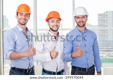 Cheerful architect and workers are giving thumbs up with joy. They have already done the work of project. The men are smiling and looking at the camera with happiness