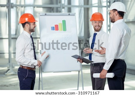 Cheerful architect is explaining to his team the main ideas of construction. He is pointing at blueprint with inspirations. The workers are smiling