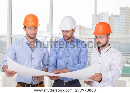 Cheerful architect is showing to builders the sketches o building. He is explaining the main ideas with seriousness. The men are looking at a paper with concentration