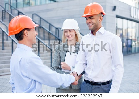 Cheerful architects are shaking hands and greeting each other. The men are standing and smiling. The woman in white helmet is holding a folder of documents. She is looking at builders happily