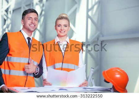Cheerful architects are standing near a table with blueprints on it. They are creating a new project and smiling. The man is giving thumb up. The woman is holding a paper of sketches - stock photo