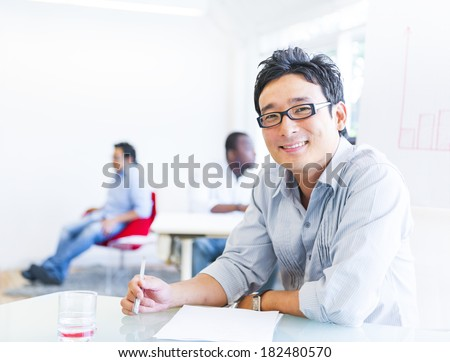 Cheerful Asian Businessman Working in Office - stock photo