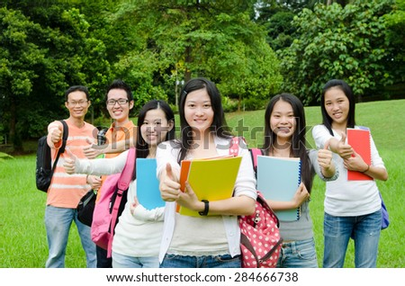 Cheerful asian college students raised their thumbs up - stock photo