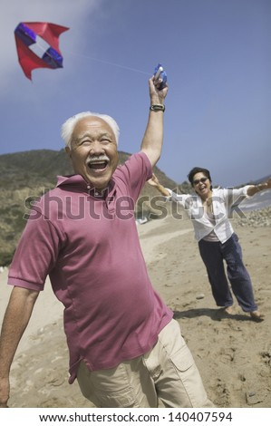 Cheerful Asian couple flying kite on the beach - stock photo