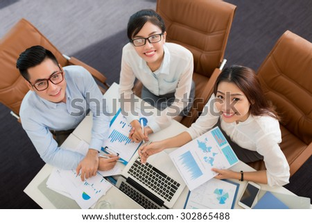 Cheerful Asian coworkers sitting at the table with business documents and looking up - stock photo