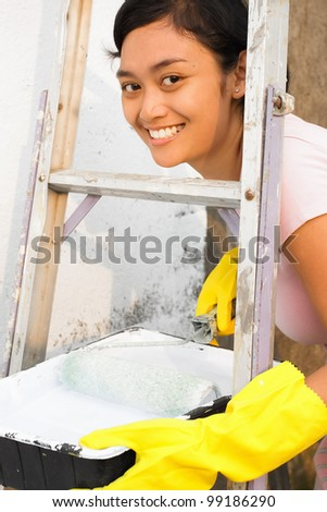 cheerful asian ethnic young adult female happy doing house painting - stock photo