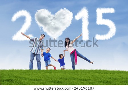 Cheerful asian family holding hands in meadow under cloud of 2015
