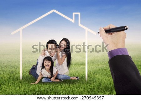 Cheerful asian family laughing together on the meadow under a dream house