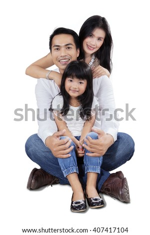 Cheerful Asian family smiling at the camera while sitting on the floor in the studio, isolated on white background - stock photo
