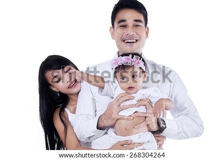 Cheerful asian family standing in studio, isolated over white background - stock photo