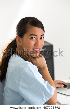 Cheerful Asian female doctor looking at the camera - stock photo