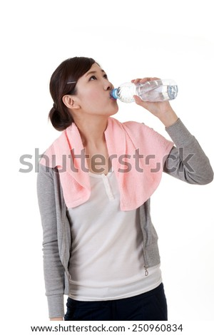 Cheerful Asian girl holding bottle of water, closeup portrait with towel on shoulder on white background.