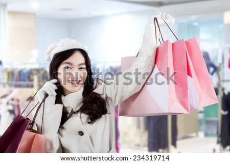 Cheerful asian girl holding shopping bags and smiling at the camera in the mall