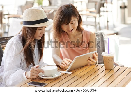 Cheerful Asian girl showing something on digital tablet to her friend - stock photo