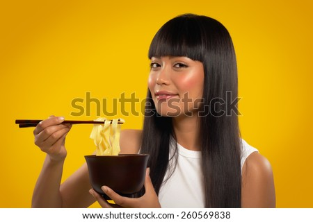 Cheerful Asian girl with noodles and chopsticks. - stock photo