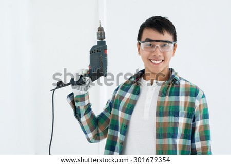 Cheerful Asian handy man in goggles holding a drill - stock photo