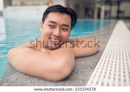 Cheerful Asian man at the edge of the swimming pool - stock photo