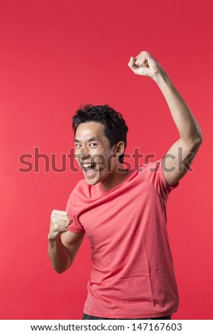 Cheerful Asian man celebrating with his arm up. In front of Red background.