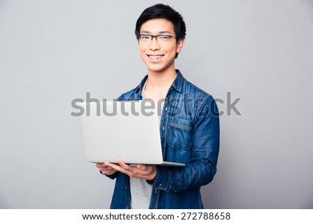 Cheerful asian man standing with laptop over gray background. Looking at camera