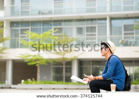 Cheerful Asian man with phone and newspaper resting on bench outdoors - stock photo