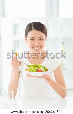 Cheerful Asian woman eating salad - stock photo