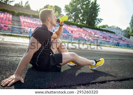 Cheerful athlete is sitting on road in stadium. He is drinking water from bottle. His eyes are closed with pleasure - stock photo