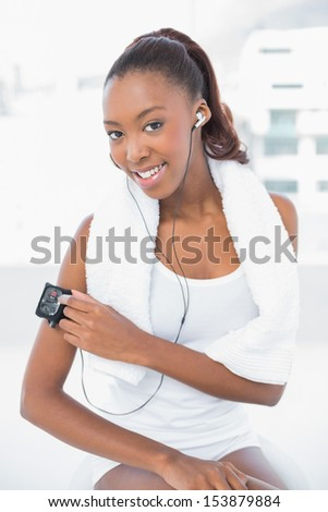 Cheerful athletic woman changing music on her mp3 in bright fitness studio