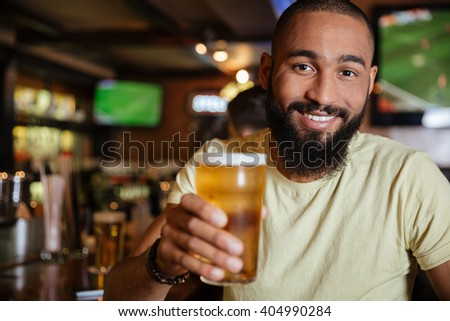 Cheerful attractive african american young man drinking beer in pub - stock photo