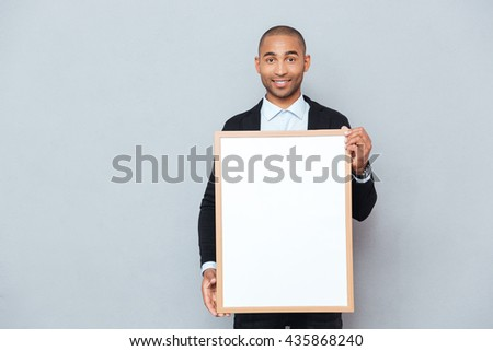 Cheerful attractive african man standing and holding whiteboard - stock photo