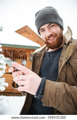 Cheerful attractive bearded man using mobile phone standing in front of log cabine in winter  - stock photo