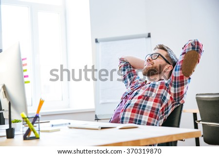 Cheerful attractive bearded young man sitting on workplace with hands behind head and relaxing - stock photo