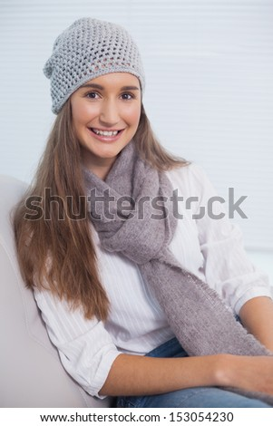 Cheerful attractive brunette with winter hat on posing in bright living room - stock photo