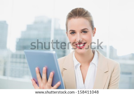 Cheerful attractive businesswoman in bright office using her tablet