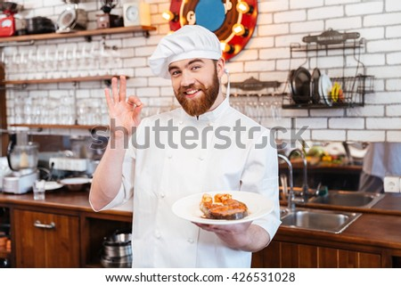Cheerful attractive chef cook holding prepared salmon steak on plate and showing ok gesture on the kitchen - stock photo