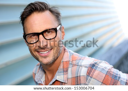 Cheerful attractive man with stylish eyeglasses on - stock photo