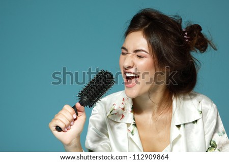 Cheerful attractive teen girl sing song holding comb like a microphone in the morning. Over blue background. - stock photo