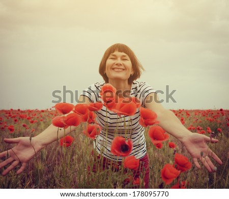 Cheerful attractive woman has fun on a poppy field, summer outdoor. Image toned. - stock photo