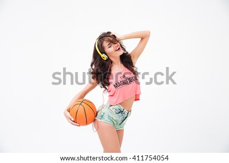 Cheerful attractive woman holding basketball ball and listening music in headphones isolated on a white background - stock photo