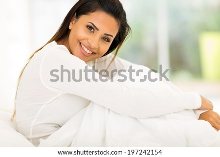 cheerful attractive woman sitting on bed at home - stock photo