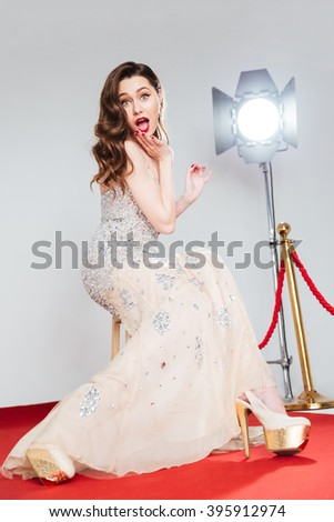 Cheerful attractive woman sitting on the chair on red carpet and looking at camera - stock photo